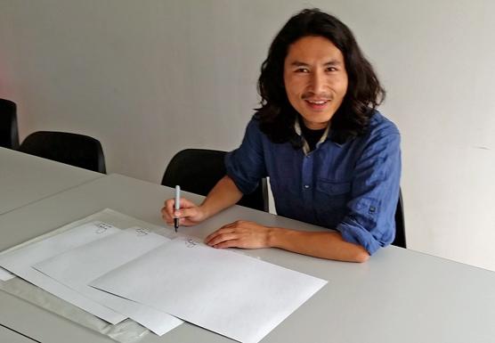 Tsering signing the photos.