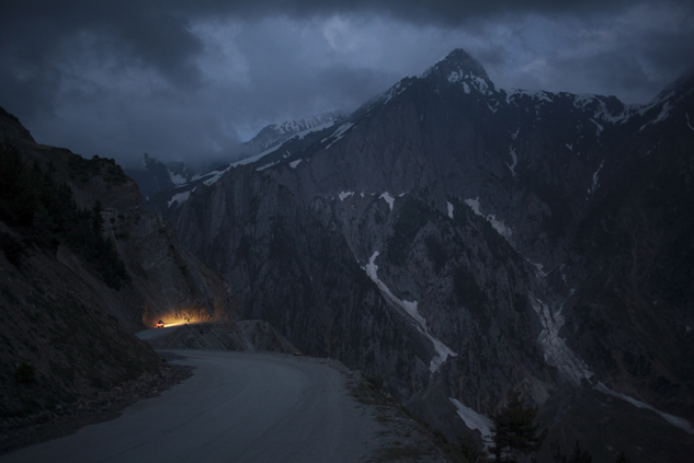 A car moves on a serpentine road past snow-capped peaks near Zoji La in Indian-Kashmir, India. Many Tibetans say that being in the mountains make them miss their homeland.