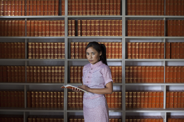 Kalsang, 19, poses for a photo at a Tibetan college library near Dharmsala, India. She escaped from Tibet into India in 2004 and says she misses her parents more as she grows older. Kalsang is currently studying Buddhism and says it helps her understand the world and to be in control of her emotions.