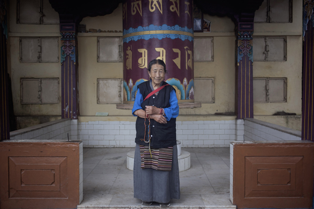 Sonam Dolma, 75, poses near a prayer wheel in Dharamsala, India. Dolma escaped from Tibet in 1959 and made Dharmsala her home. She says she wishes to visit Tibet someday.