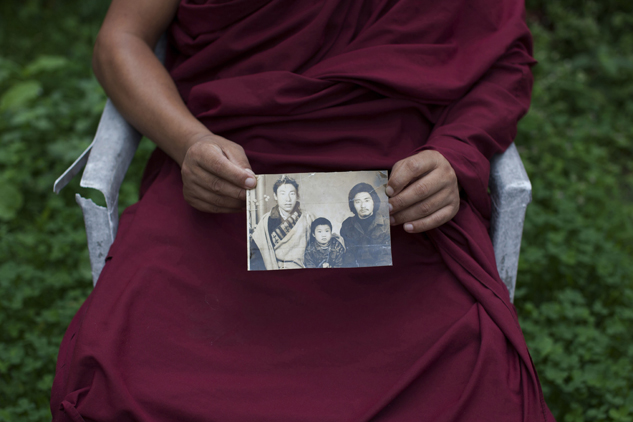 Tibetan monk Dorjee, 38, displays a photograph of his father, left, and himself, center, taken in Tibet, in Dharamsala, India. Dorjee said he held back his tears when he spoke with his parents on the phone after a separation period of 27 years. He exchanged a few words with his father but said his mother fainted on hearing his voice.