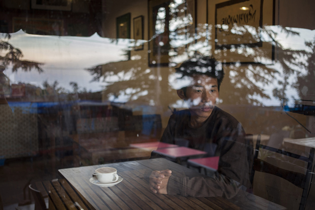 Tashi Dorjee 27, sits in a coffee shop in Dharmsala, India. He fled with his brother as a four-year-old in 1991. Dorjee says he missed his parents most when he was in school, especially when everyone went home for winter vacation as he had no home to go to. He says because of time and distance there is no attachment with family and parents.