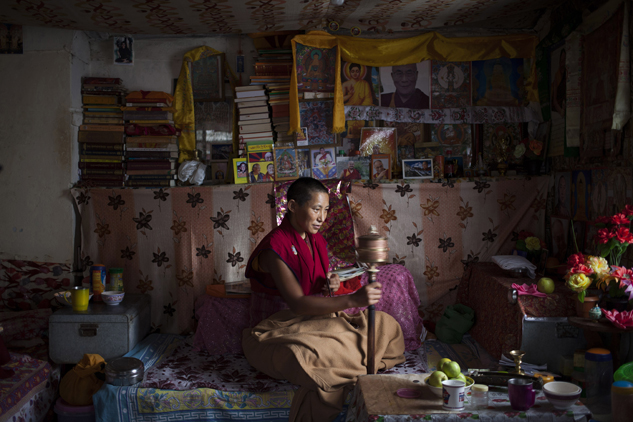 Namdak Choeying, 44, prays in her small room that she shares with two other nuns in Dharmsala, India. Back home in Tibet she aspired to be a fully ordained nun and escaped to India in 2006. Her five siblings and aged parents live in Tibet and she dreams about meeting them. Choeying said she immerses herself in prayers to keep her mind occupied.